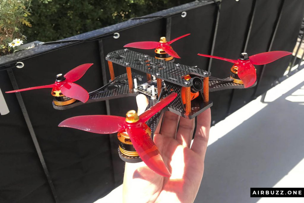 Drone with red props with orange motors, camera and standoffs.
